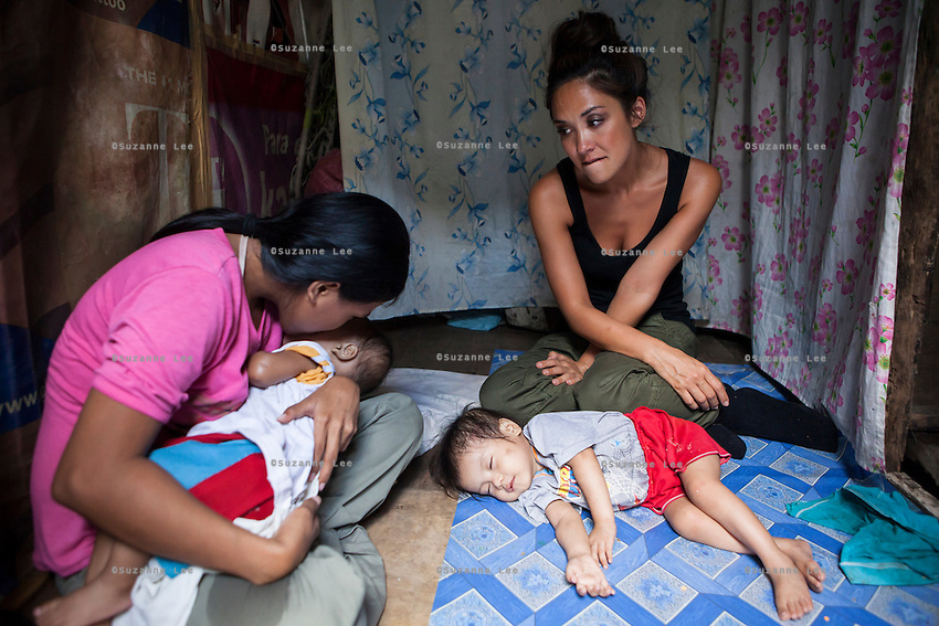 UK celebrity Myleene Klass weeps as Vilma Tacuyo, 20, kisses her youngest child, Ulderico (10 months), in their one room home in an urban slum in Paranaque City, Metro Manila, The Philippines on 18 January 2013. Vilma had raised her first 3 children on formula and had to cut down on food for her family to afford it. Both John Ashley, 4, and Justin (sleeping), 3, are malnourished and stunted, and after losing one of her children, she now breastfeeds her youngest, Ulderico. Photo by Suzanne Lee for Save the Children UK