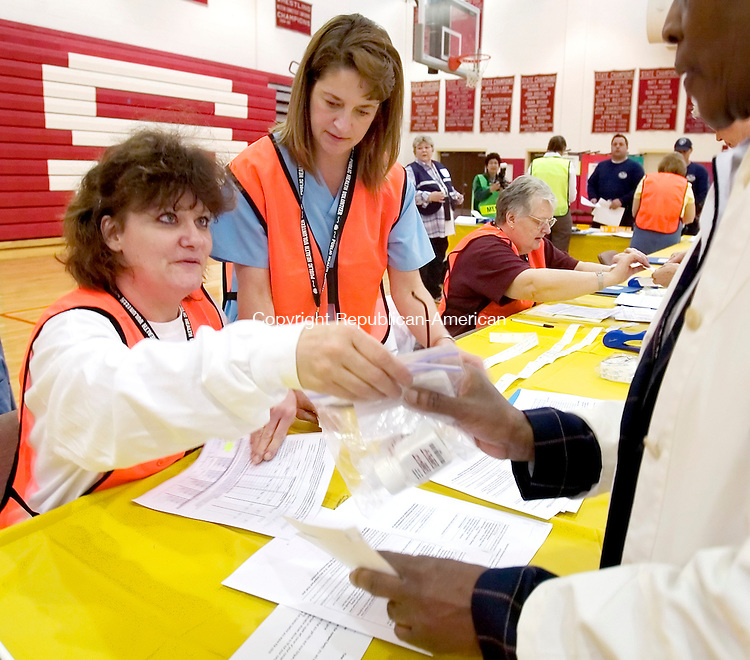 SOUTHBURY, CT. 19 April 2006-041906SV02--From left, Holly Gunning and Donna Fenwick, volunteers from Southbury Training School, pass out medication during public health drill at Pomperaug High School in Southbury Wednesday.<br /> Steven Valenti Republican-American