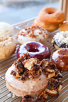 Bluestar Donuts featuring, Fried Chicken over original glazed (front center) - Chocoalate Cocnut Ganache -Creme Brûlée w/ vanilla custard - Blueberry, Bourbon, Basil - Meyer Lemon & key lime curd - Real Maple and bacon - original glazed -