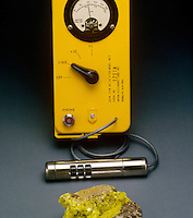 GEIGER COUNTER AND URANIUM MINERAL AUTUNITE<br /> Uranium Ore Radioactivity Measured<br /> A gas mixture (either argon and ethanol or neon and bromine) inside the Geiger counter cylinder, with high potential difference between central wire and walls of cylinder. Radiation ionizes the gas, resulting in one click per nuclear disintegration unit.