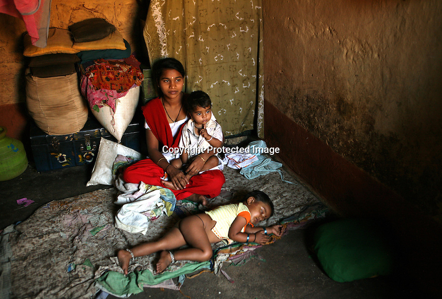 "Kavita Kurbati, 18, sits inside her family home in the bustling town of Gokak, India, waiting for a customer. In her arms is daughter Chaitra (1) and sleeping peacefully at her feet is Rakshita (3). When Kavita reached puberty, her mother, drawing on an ancient religious tradition, dedicated her to the Hindu deity, Yellamma, thus turning her daughter into a Devadasi or ""female servant of god"". This meant that Kavita was ""married"" to Yellamma, which made her ineligible to marry a mortal. Instead, as a means of pleasing Yellamma and bringing better fortunes to her family, she would serve as a ""temple prostitute"", satisfying the needs of men in her community."