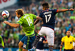 Seattle Sounders Chad Marshall (14) heads the ball away from  New England Revolution Juan Agudelo (17) during an MLS match on March 8, 2015 in Seattle, Washington.  The Sounders beat the Revolution 3-0.  Jim Bryant Photo. ©2015. All Rights Reserved.