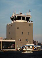 Airtraffic control tower and a parked helicopter in the foreground.  May not be used in an elementary school dictionary. Cleveland Ohio USA.