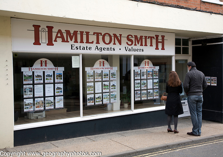 Young couple looking in estate agent shop window Woodbridge Suffolk