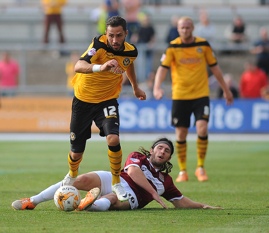 Newport County's Robbie Willmott is tackled by Northampton Town's John-Joe O'Toole<br /> <br /> Photographer Kevin Barnes/CameraSport<br /> <br /> Football - The Football League Sky Bet League Two - Newport County AFC v Northampton Town - Saturday 13th September 2014 - Rodney Parade - Newport<br /> <br /> &copy; CameraSport - 43 Linden Ave. Countesthorpe. Leicester. England. LE8 5PG - Tel: +44 (0) 116 277 4147 - admin@camerasport.com - www.camerasport.com