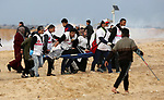 Paramedicals carry a wounded Palestinian protester, who was injured by Israeli security forces at the Gaza-Israel maritime border, during clashes across from the Israeli settlement of Kibbutz Zikim, on  February 19, 2019, as part of weekly maritime protests against the naval blockade of the coastal enclave. At least 20 Palestinians were injured as Israeli forces suppressed the 24th naval march along the northern besieged Gaza Strip, on Tuesday afternoon. Photo by Ashraf Amra