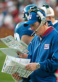Landover, MD - December 24, 2005 -- New York Giant head coach Tom Coughlin looks through his game plan to find a play that would work against the Washington Redskins at FedEx Field in Landover, MD on December 24, 2005. The Redskins won the game 35 - 20..Credit: Ron Sachs / CNP.(RESTRICTION: NO New York or New Jersey Newspapers or newspapers within a 75 mile radius of New York City)