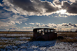 Idaho, south central, Shoshone. An old rusted automobile in a field in winter.