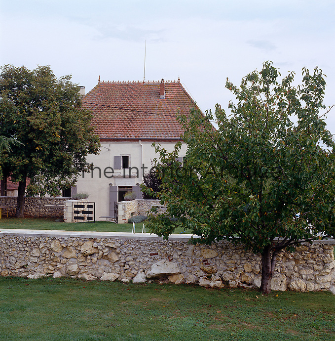 The exterior and garden of a restored French house which is home to a collection of modern design classics