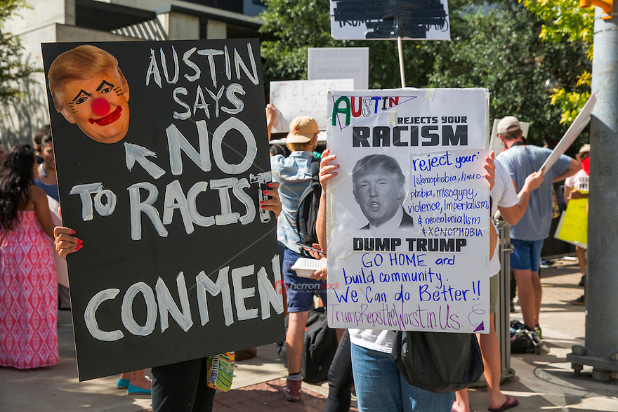 Protesters hold up signs against Republican presidential candidate Donald Trump outside while Trump makes an appearance at a taping of a two-hour interview with Fox News host Sean Hannity at ACL Live at The Moody Theater in downtown Austin, Texas.<br />