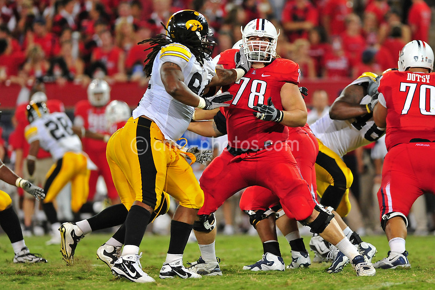 Sept 18, 2010; Tucson, AZ, USA; Arizona Wildcats offensive tackle Adam Grant (78) takes a hand to the face from Iowa Hawkeyes defensive end Adrian Clayborn (94) in the 3rd quarter of a game at Arizona Stadium.  Arizona won the game 34-27.