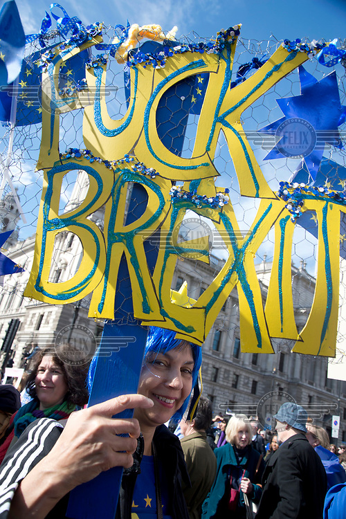 A woman carries a sign made up of cut-out letters that annouces: 'Fuck Brexit' at a 'Unite for Europe March on Parliament'.