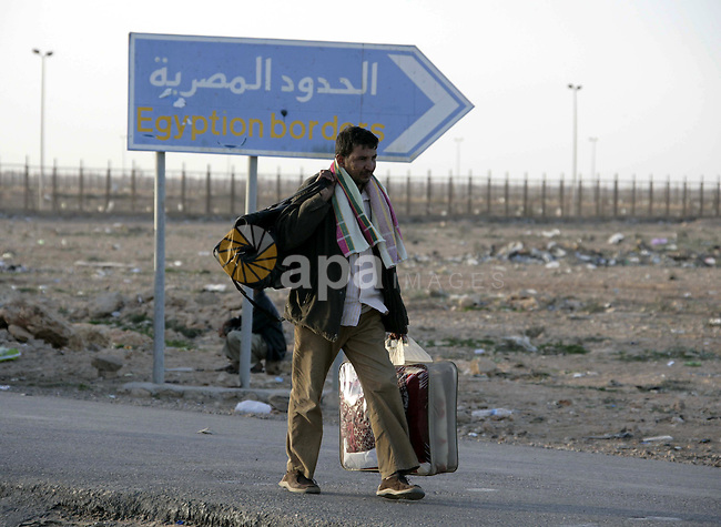 An Egyptian man, who has fled from Libya through the Salloum land port gate walks with has luggage,Tuesday, Feb. 22, 2011. An estimated 5,000 Egyptians have returned home from Libya by land, and about 10,000 more are waiting to cross the Libya-Egypt border, an Egyptian security official said. Egypt says it will also send six commercial and two military planes to repatriate thousands more caught in the revolt against Moammar Gadhafi's regime. Photo by Karam Nasser