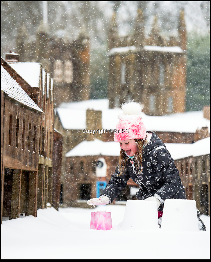 BNPS.co.uk (01202 558833)Pic: PhilYeomans/BNPS<br /> <br /> Schools Out - Florence Angus (6) make's the most of the snowfall in the lilliputian surroundings of Wimborne Model Town in Dorset.