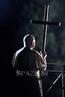Pope Benedict XVI prays as a faithful holds the cross during the traditional Via Crucis (Way of the Cross) at the Colosseum in Rome April 6, 2007..