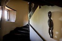 A small lead-paned window illuminates the winding oak staircase