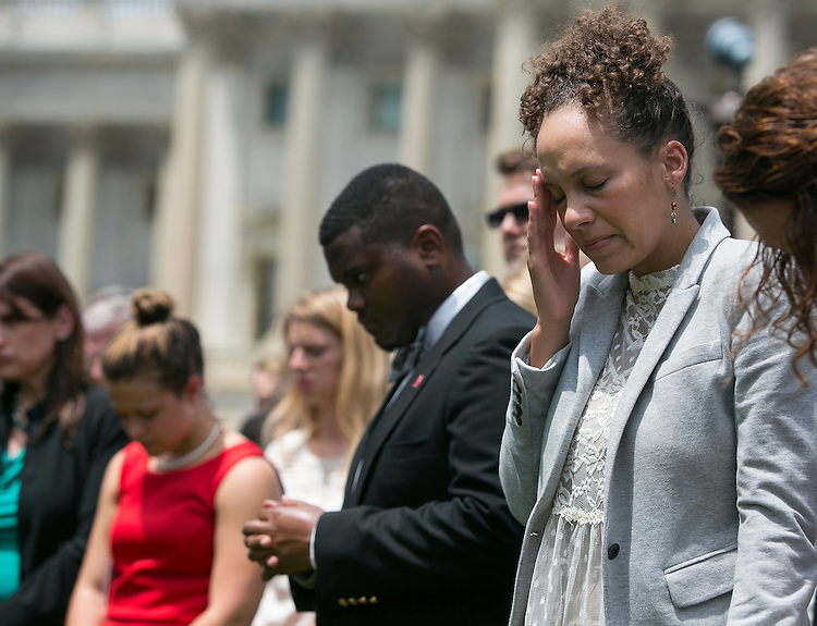 UNITED STATES - JUNE 18 - Jennifer DeCasper, Chief of Staff for Sen. Tim Scott, R-S.C., holds her head as she listens to a prayer vigil for victims of the Charleston shooting, outside of the U.S. Capitol on Thursday, June 18, 2015. (Photo By Al Drago/CQ Roll Call)