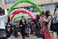 A teacher leads Elementary school children through arches of paper flowers to celebrate their graduation from Elementary school. Tsukushino, Tokyo, Japan. Thursday March 24th 2016