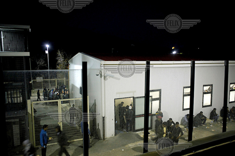 Illegal immigrants hang around outside at the reception centre at night. Since the beginning of revolutions in their countries, hundreds of Libyan and Tunisian people a day cross from the northern coast of Africa to Lampedusa. About 90% of them are Tunisian.