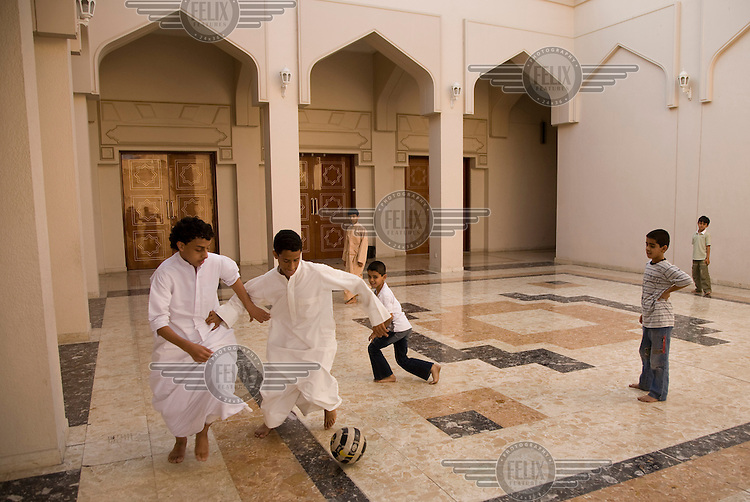 Children playing football in the courtyard of a mosque in the Bastakia Quarter of Old Dubai.