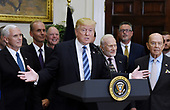 United States President Donald J. Trump, flanked by Vice-President Mike Pence (L), Apollo 11 astronaut Buzz Aldrin (3-L) and Commerce Secretary Wilbur Ross (R) speaks before signing an Executive Order to reestablish the National Space Council  in the Roosevelt Room of the White House in Washington, DC, on June 30, 2017. <br /> Credit: Olivier Douliery / Pool via CNP