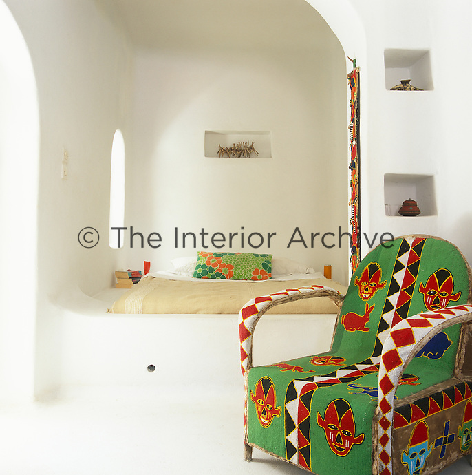 A brightly coloured Masai beaded chair in a simple whitewashed bedroom