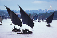 Against the almost unearthly backdrop of the Shwedagon Pagoda's golden stupa in Rangoon, Burma, fishing boats sail home up the Rangoon River.