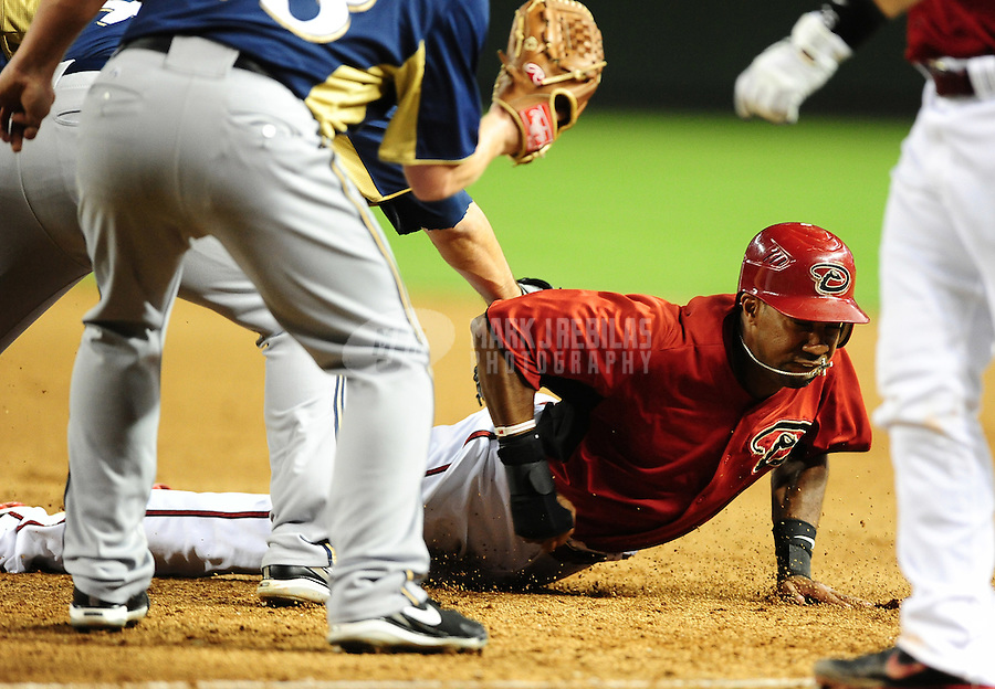Apr. 3, 2012; Phoenix, AZ, USA; Arizona Diamondbacks base runner Chris Young dives safely into first base after being caught in a fourth inning rundown against the Milwaukee Brewers during a spring training game at Chase Field.  Mandatory Credit: Mark J. Rebilas-.