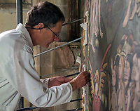 BNPS.co.uk (01202 558833)<br /> Pic: PeterMartindale/BNPS<br /> <br /> Conservator Peter Martindale injected lime slurry to stabilize the fresco.<br /> <br /> Doom finally has its day! - A 500 year old 'Day of Judgement' painting, that has survived Henry VIII th, the Puritans and even Victorian prudery has been restored to its former glory.<br /> <br /> Thought to be the largest medieval 'Doom' painting in the country, the striking image been painstakingly restored after a tumultuous 500 year history on the chancel arch of St Thomas Becket church in Salisbury.<br /> <br /> Originally painted in the 15th century, the chancel was white-washed during the Reformation before being uncovered nearly 300 years later in the early 19th century. <br /> <br /> Prudish Victorian's shocked by the naked images then recovered it before it finally re-emerged in 1881 as opinions relaxed. <br /> <br /> Experts have spent three months conserving the faded painting, which included injecting lime slurry behind areas of paint to affix them again to the wall. and delicately 'touching up' in places before finishing it with varnish to bring out its colour.<br /> <br /> Most pre 16th century churches and cathedrals in Britain would have been plastered with religious images and iconography to encourage their often illiterate congregation to good behaviour.<br /> <br /> But during Henry VIII th Protestant Reformation churches were stripped of all graven imagery and the paintings were either whitewashed over or completely destroyed.<br /> <br /> Because of this very few works still survive today making the Salisbury fresco a truly remarkable survivor.<br /> <br /> The restoration is part of a larger set of works at the historic church which are due to cost £1.5million.