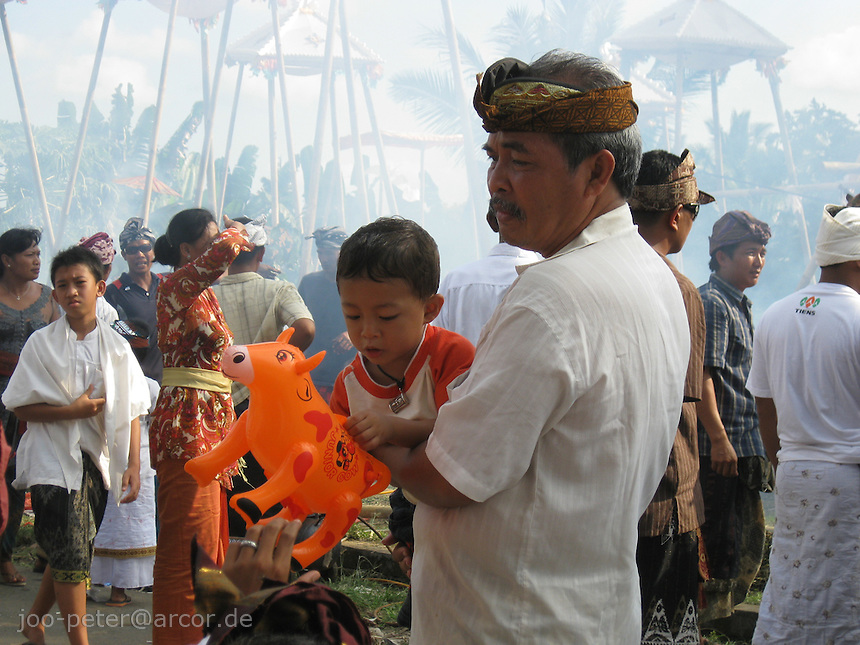 a small gift cheers up the youngest while cremation ceremonies in Petulu, Bali, archipelago Indonesia