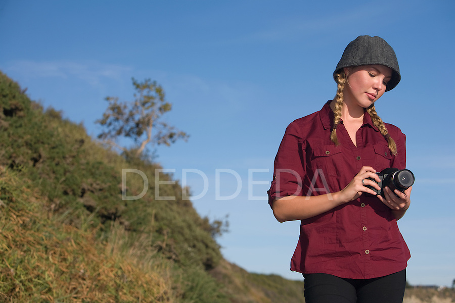 A pretty female photographer holds her camera outdoors.
