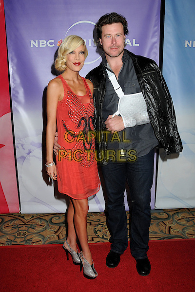 TORI SPELLING & DEAN McDERMOTT.NBC Universal Press Tour Cocktail Party held at the Langham Hotel, Pasadena, California, USA, 10th January 2010..full length red sleeveless dress married couple husband wife black leather jacket arm in sling injured injury sheer mesh beaded pattern grey gray platform slingbacks shoes jeans snakeskin snake print .CAP/ADM/BP.©Byron Purvis/AdMedia/Capital Pictures.