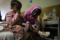 Emembet Albachew, 26 years old, HIV positive, massages her daughter Magdass while hospitalized at the St Paul public hospital in Addis Ababa, Ethiopia on Friday June 30 2006. Emembet lives with her daughter, 3 years old Magdass, her only reason to live. On June 20th she was reported to be dead by the St Paul hospital staff while she was enduring a deep physical crises. after almost 4 weeks of hospitalization she was discharged and could finally reunite with her daughter that meanwhile lived with a local home base care giver. . Ethiopia is one of the countries most affected by HIV/AIDS. Of its population of 77 million, three million are HIV-positive, according to government statistics. Every day sees 1,000 new infections. A million children under 14 have lost one or both parents to AIDS, and 200,000 children are living with AIDS. That makes Ethiopia the country with the most HIV-positive children.