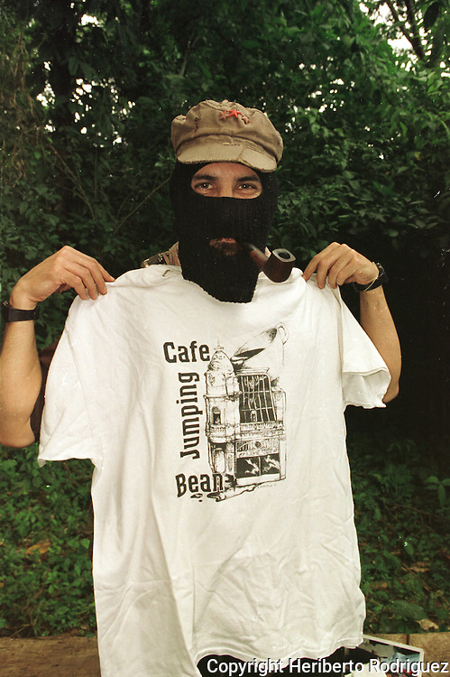 Subcomandante Marcos, the leader of the Zapatista National Liberation Army (EZLN), shows a T-shirt with a logo of the Chicago coffee shop Jumping Bean Cafe after an interview with the photographer in his stronghold of La Realidad village in southern Chiapas state. Photo by Heriberto Rodriguez