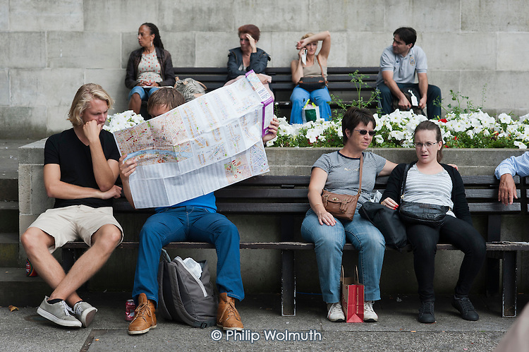 Tourists resting on benches at Marble Arch look at a map.