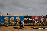 SOWETO, JOHANNESBURG, SOUTH AFRICA - DECEMBER 08: Parishioners walk past a mural depitcing the former Presidnet Nelson Mandela after having offered prayers during Sunday mass at the Regina Mundi Roman Catholic church in Soweto on December 8, 2013 in Johannesburg, South Africa. Mr Mandela, died on Thursday aged 95, spent 27 years in jail before becoming South Africa's first black president in 1994.<br /> Photo by Daniel Berehulak for The New York Times
