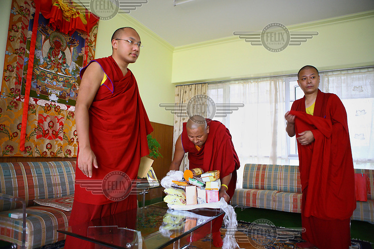 The Seventeenth Karmapa, Ogyen Drodul Trinley Dorje (left), receives gifts from an audience at the Gyuto Tantric Monastic University, Dharamsala. In 1992 a 7-year-old Tibetan nomad, Apo Gaga, was recognised as the Seventeenth Karmapa and went to live in Tolung Tsurphu Monastery, the historic seat of the Karmapas. He escaped Tibet for India at the turn of the millennium in order to continue without interference the primary role of the Karmapa, preserving and propagating the Buddhist teachings of Tibet.