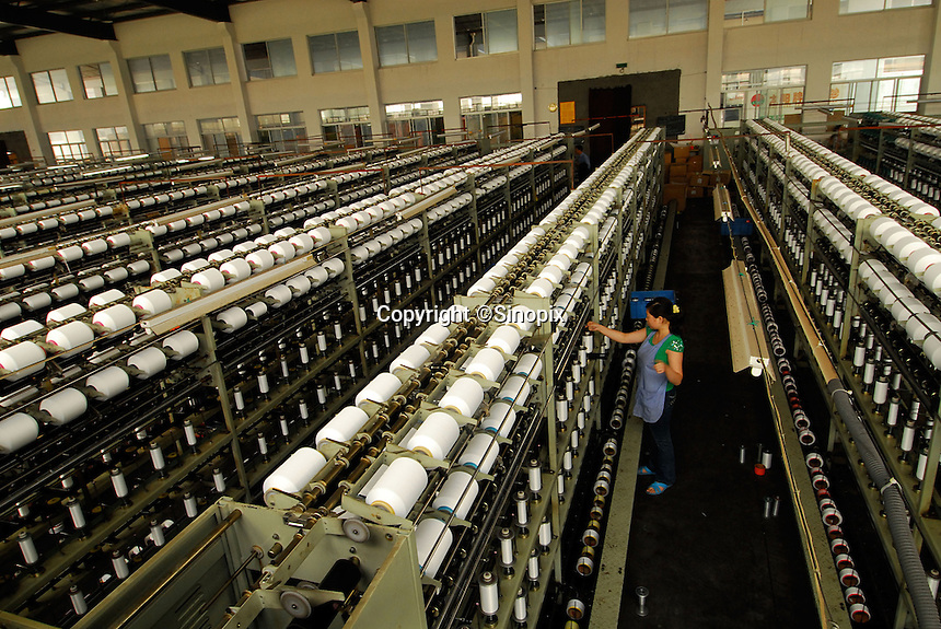 "The spinning room at Taiming Chemical Fibre Limited in ""Datang Sock Town"" in Zhuji City Zhejiang Province, China. The factory, one of several spinning factories,  runs 24 hours a day producing over 100,000 spools of nylon yarn per day which are all consumed in Datang Town. The town makes more than 5.3 billion pairs of socks annually - that 2.5 pairs for every human alive.  Most people in the town make a living directly connected to the sock weaving industry..14 Jun 2006"