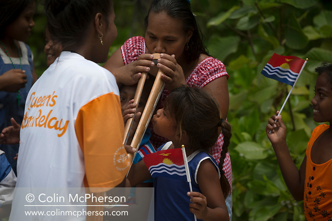 The Queen's Baton Relay spent the day on Maiana island, one of the islands of Kiribati. This Queen's Baton Relay will engage with all 70 nations and territories of the Commonwealth, over 388 days and cover 230,000km. It will be the longest Relay in Commonwealth Games history, finishing at the Opening Ceremony on the Gold Coast on 4th April 2018. Photograph shows a woman and child kissing the Baton as one of the batonbearers shows it to members of the local community during a Relay through one of the 12 villages on the island of Maiana, Kiribati.