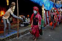 A Naga Sadhu (naked saint) offers food grain to another saint at Kumbh mela on 13th February 2010. Haridwar, Uttara Khand, India, Arindam Mukherjee
