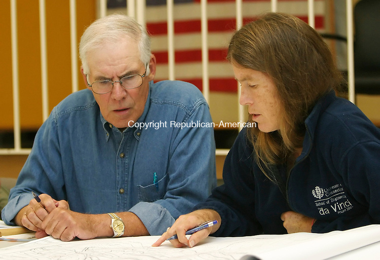 MIDDLEBURY,  CT 27 September 2005 -092705BZ07- Middlebury Conservation Commission members Jim Croccichia, left, and Melinda Burbank, right, look over plans of the Straw Pond Development during their meeting Tuesday.<br /> Jamison C. Bazinet / Republican-American