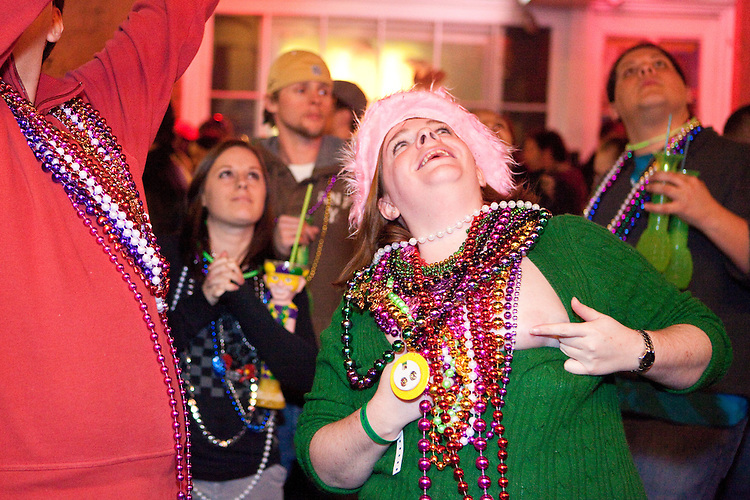 A woman exposes herself to get beads thrown from a balcony, to the delight of a crowd of men on Bourbon Street during Mardi Gras in New Orleans on February 14, 2010.