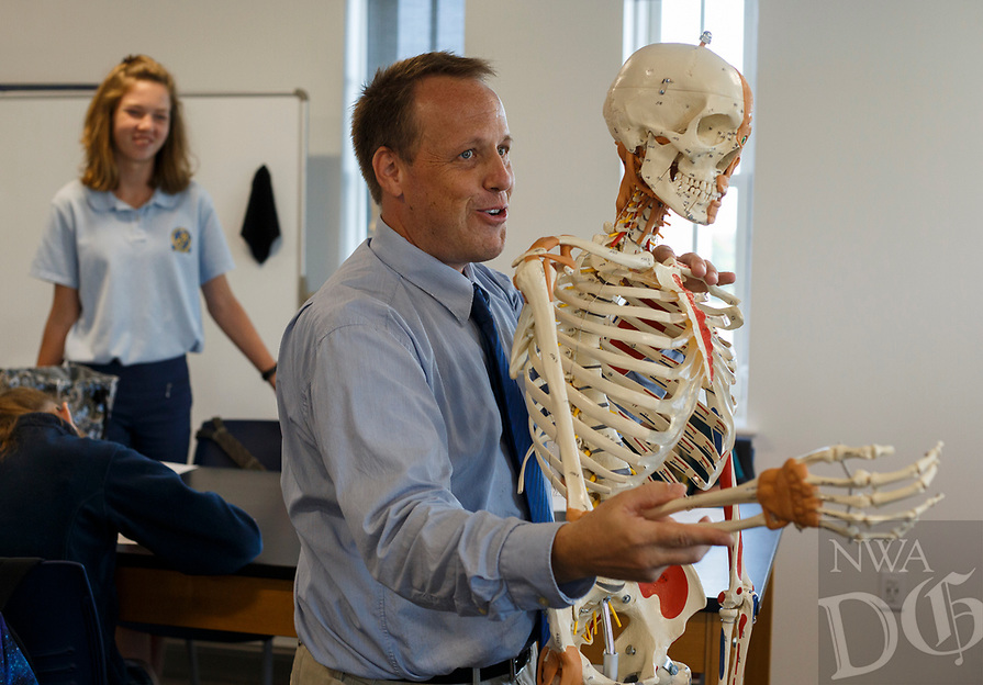 NWA Democrat-Gazette/CHARLIE KAIJO Teacher Mick Frus gives an anatomy lesson using a model skeleton during an eighth grade health class, Thursday, August 9, 2018 at Haas Hall in Rogers. <br />