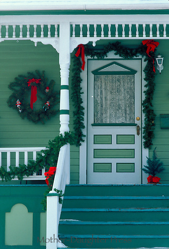 Home with front porch decorated for Christmas holidays with bows, boughts, and wreath