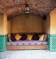 A brightly patterned carved wooden banquette filled with cushions is tucked into a barrel vaulted niche