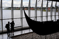 Denmark, Zealand, Roskilde: Viking age ship inside the Viking Ship Hall at the Viking Ship Museum with Roskilde Fjord behind | Daenemark, Insel Seeland, Roskilde: Ueberreste eines Vikingerschiffs im Wikingerschiffmuseum