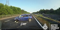"Pictured: Dashcam video grab showing a blue Mini rolling over after colliding with a silver Ford Mondeo and crashing against the barrier on the M4 motorway near Port Talbot, Wales, UK in June 2018.<br /> Re: Two motorists have been convicted of dangerous driving following a road rage incident on the M4 near Port Talbot.<br /> Dash cam footage shows the two men repeatedly undertaking and tailgating each other along the eastbound carriageway in June last year.<br /> The incident eventually led to one of the vehicles – a blue Mini – flipping onto its roof with the driver fortunate to get out of the car unharmed.<br /> Paul Carpenter, aged 44, from Boxhill in Surrey, and Wayne Sebury, 59, from Pontypridd, initially denied any wrongdoing but later pleaded guilty to dangerous driving.<br /> They appeared at Cardiff Crown Court on Thursday 11th April where Carpenter was sentenced to six months in prison and disqualified from driving for 18 months. Sebury was given an 18 month community order and disqualified for 12 months. He must also carry out 150 hours unpaid work.<br /> PC Kathryn Matthews of the South Wales Police Roads Policing Unit said: ""This incident was a classic case of road rage where two motorists have driven dangerously, at high speeds, undertaking, tailgating and flashing their lights.<br /> ""It is sheer luck that nobody was killed or seriously injured and the dash cam footage of the incident sends out a clear message about the consequences of driving in such an irresponsible manner.""<br /> Expert witness evidence showed that Sebury drove his blue Mini and Carpenter his Ford Mondeo at speeds of upto 101mph shortly prior to the collision."