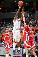 Dec. 07, 2010; Charlottesville, VA, USA;  Virginia Cavaliers forward Akil Mitchell (25) shoots between Radford Highlanders guard Jeremy Robinson (1) and Radford Highlanders forward Tolga Cerrah (41) during the game at the John Paul Jones Arena. Virginia won 54-44. Mandatory Credit: Andrew Shurtleff