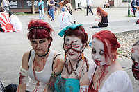 3 female participants in the prague zombie walk 2014 looking at the camera, all 3 have red hair and have fake blood on them 2 wearing white clothes the femal in the middle is wearing a turquise blouse. Background other participants.