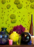 "In the living room a collection of opaque and transparent Murano glass is displayed in front of a vivid lime-green piece entitled ""Garancia"" by Andrea di Vitis"
